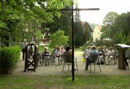 Eine Gruppe von Menschen sitzt versammelt um ein Kreuz.