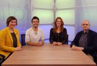 Zeigt Personen an einem Tisch im TV-Studio