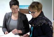 Das Bild zeigt Frauen an einem Tisch stehend. Beide Frauen sind im Bereich Prävention tätig.