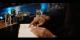 Bild zeigt eine Hand, die mit einem Finger auf eine Karte in einer Bar zeigt. Ausschnitt aus dem Werbespot zur Kirchenwahl am 1. Dezember 2019.